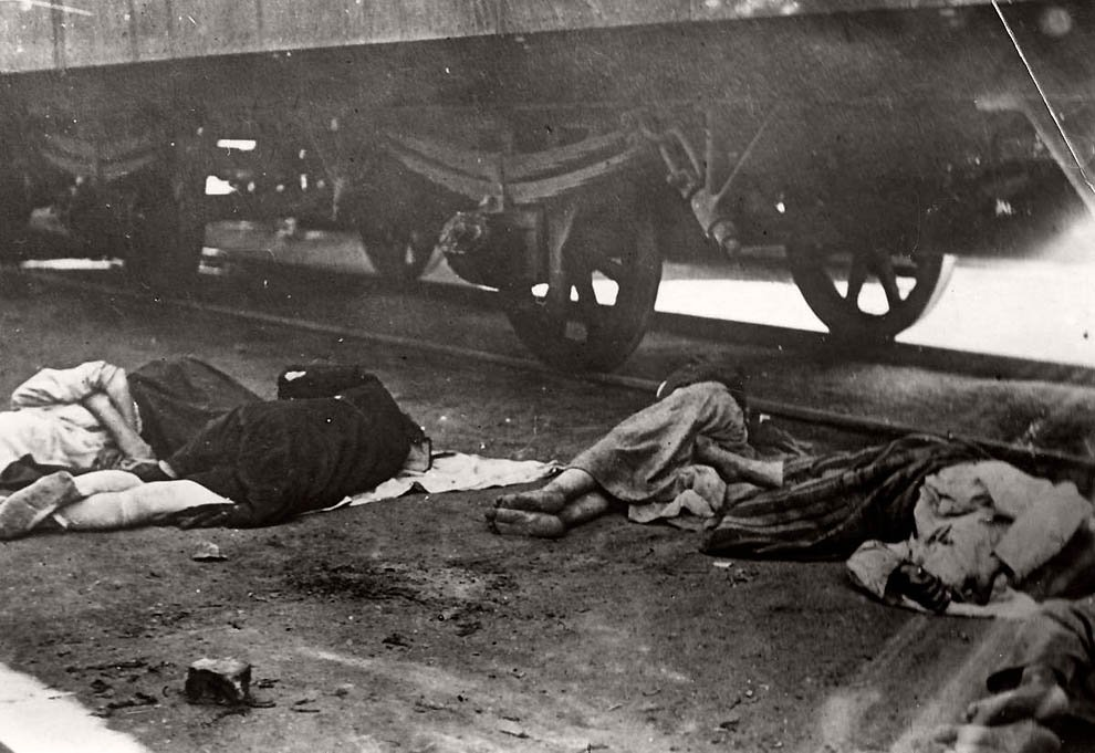Жертвы голода в Поволжье разбросаны по земле возле железнодорожных путей.